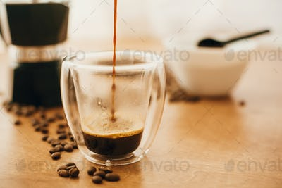 Pouring hot coffee in glass cup