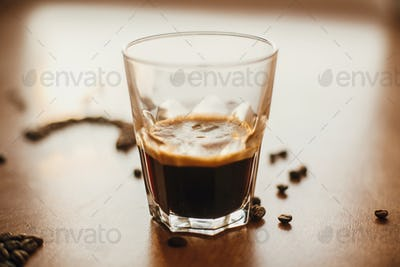 Hot espresso with foam in glass cup with aromatic roasted coffee beans