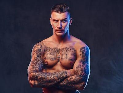 A muscular tattooed man over dark background.