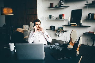 Thoughtful man sitting with feet on table and talking on phone in modern office.