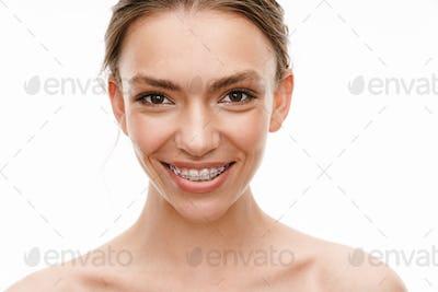 Image of beautiful caucasian young shirtless woman wearing braces