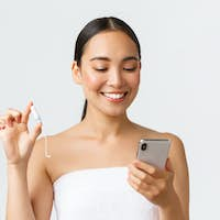 Beauty, personal and intimate care, mobile application concept. Smiling pretty asian girl having
