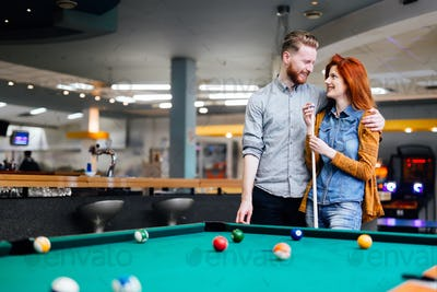Happy couple playing snooker