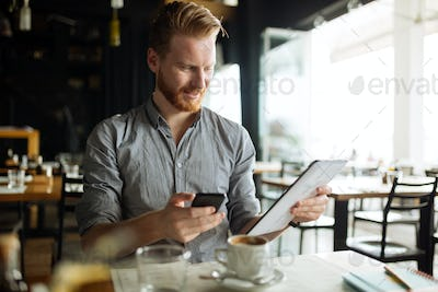 Handsome smart businessman constantly busy and working
