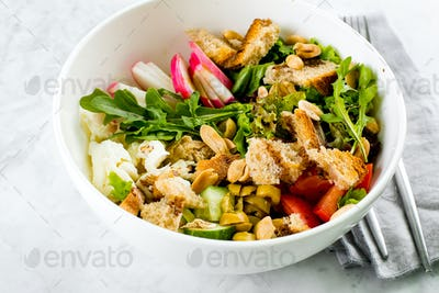 Healthy Salad Bowl. Mozzarella, vegetables, green leaves, green olives, whole grain bread, peanuts