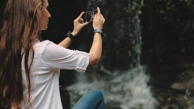 young woman traveler near waterfall at rainforest