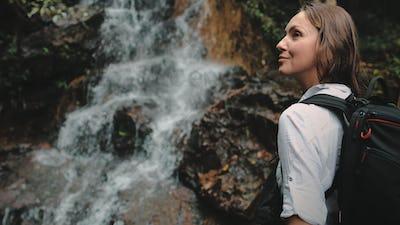 girl backpacker look at jungle cascade waterfall