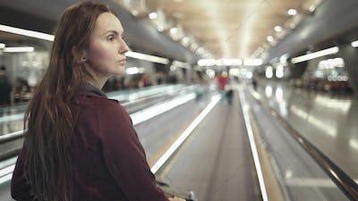 woman walking on speedwalk at airport terminal