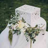 Gift box on table with floral arrangement