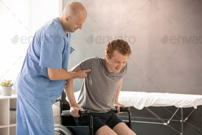 Bald clinician in uniform helping young man to sit in wheelchair after training