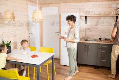 Happy young woman with bottle of milk and glass moving towards her kids