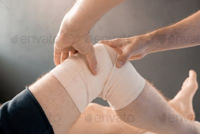 Hands of contemporary clinician massaging knee of young male patient