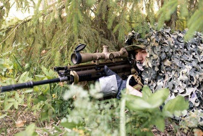 Sniper looking through rifle scope