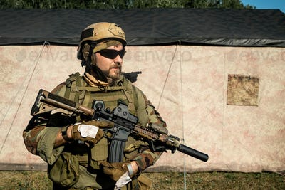 Bearded soldier in camouflage outfit holding rifle