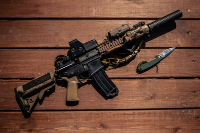 Rifle and knife on wooden table