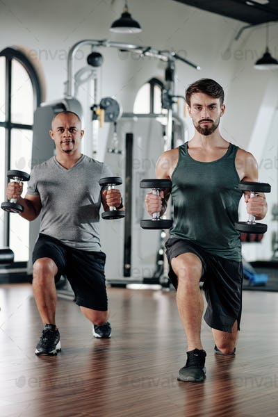 Men doing lunges with weights