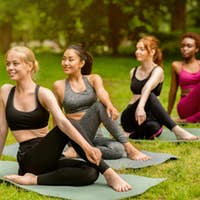 Group of multinational women attending outdoor yoga practice at park