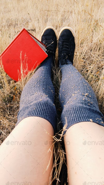 Young woman legs near a red book