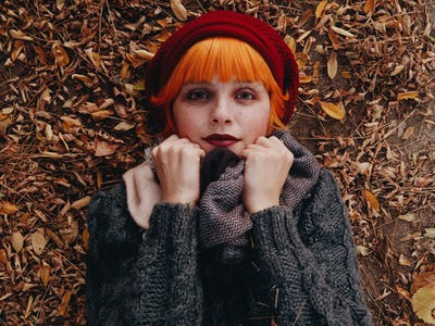 Young and redhead woman posing in an autumn scenery
