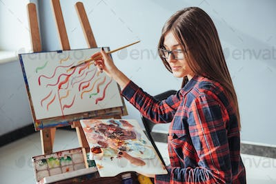 Pretty Pretty Girl artist paints on canvas painting on the easel.