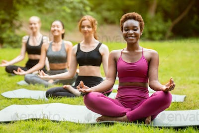 Beautiful black woman with her friends meditating on group yoga class at park, copy space