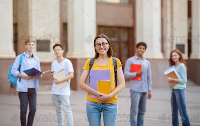 Student Girl Standing Near University Building Outdoors, Posing With Backpack
