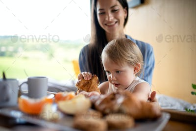 Young woman with small daughter indoors, weekend away in container house in countryside