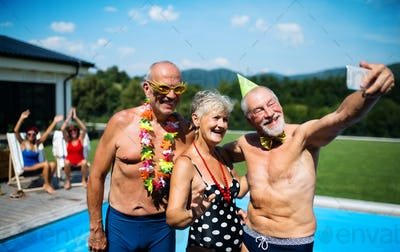 Group of cheerful seniors by swimming pool outdoors in backyard, taking selfie