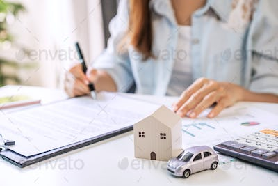 Young woman is signing a loan agreement to buy a house and a car at real estate agent office