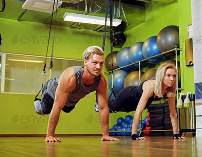 Sporty male and female doing trx straps exercises in a gym club.