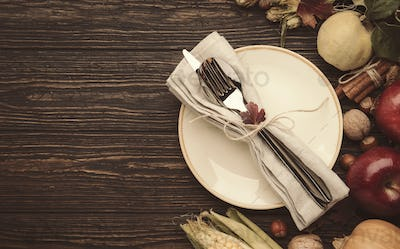 Thanksgiving dinner setting. Autumn fruit, pumpkins, nuts, fallen leaves with plate and cutlery