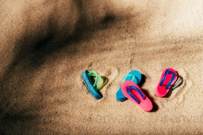 Two pairs of beach sandals or thongs on a sandy beach under the palm shade.
