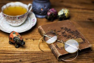 old book on the wooden desk, vintage eyeglasses, porcelain cup of tea and saucer
