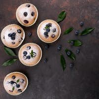 Blueberry muffins on wood background