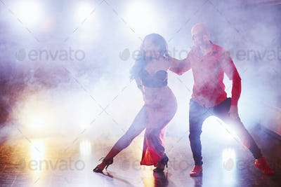 Skillful dancers performing in the dark room under the concert light and smoke