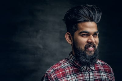 A handsome bearded Indian male dressed in a fleece shirt.