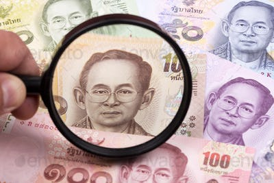 Thai money in a magnifying glass