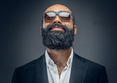 Portrait of bearded male in a suit and sunglasses.