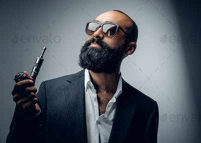 Male in a suit and sunglasses holding electronic pipe.