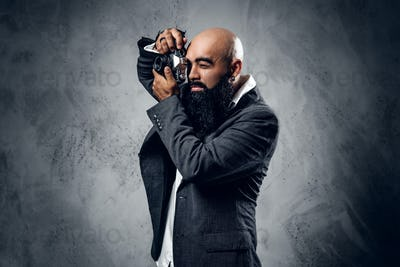 Professional photographer in a suit shooting with a compact DSLR camera.