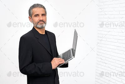Bearded man in black outfit holding laptop