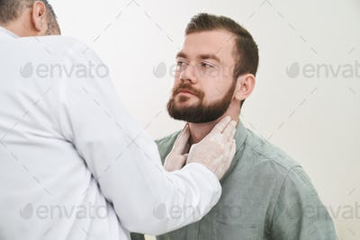 Bearded handsome man having neck and lymph nodes checked