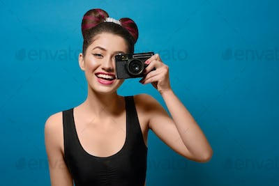 Smiling, happy girl taking photo with old camera