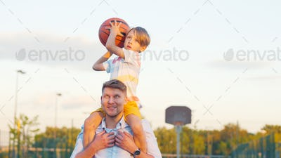 Son on father's shoulders throwing a ball