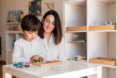 Kid playing with a tetris wood puzzle and mother or teacher help. Homeshooling.