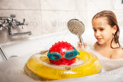 Funny little unidentified girl showering a head made of a ball
