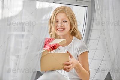 Happy daughter sitting near window, holding present