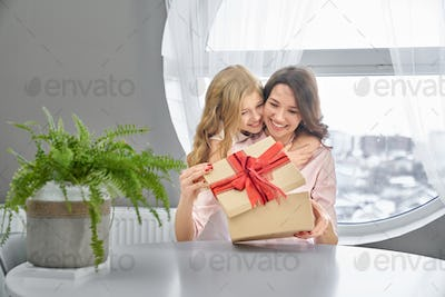 Daughter and mother hugging and smilling
