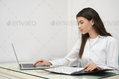 Young woman, doctor working with notebook in clinic