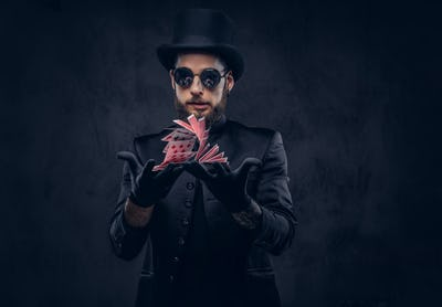 Magician showing trick with playing cards.